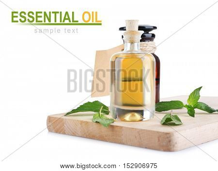 Spa composition with essence and mint, closeup. Text ESSENTIAL OIL on white background. Spa beauty concept.