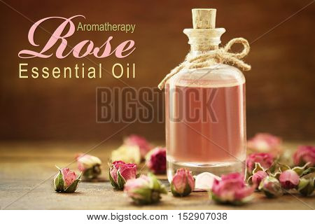 Glass bottle of essence, closeup. Text ROSE ESSENTIAL OIL on blurred background. Spa beauty concept.
