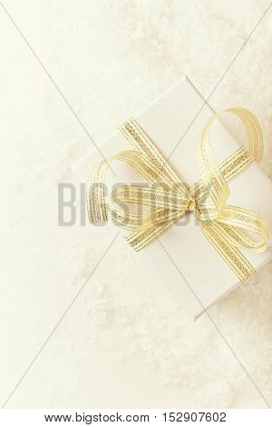 White Christmas gift with a golden ribbon