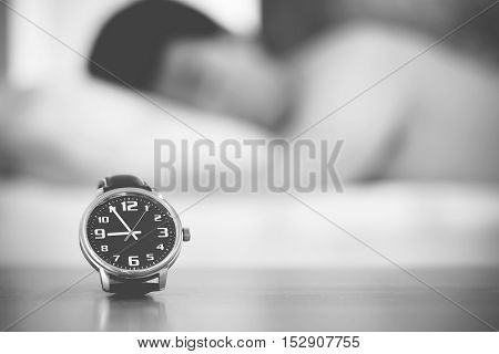 - close up on wristwatch and sleeping man on bed background