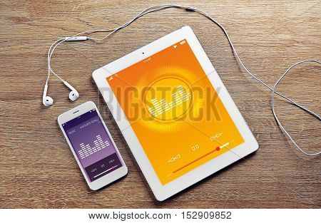 Tablet, smartphone and earphones on wooden background. Music player interface on screen.