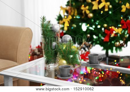 Table with cups, vases and Christmas decor on blurred background, close up view