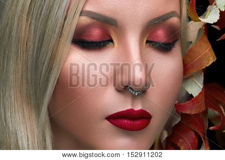 Beautiful fashion model with red , lips creative eye makeup, autumn dry leaves