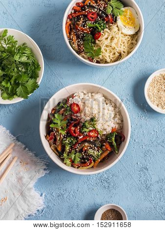 Vegetarian lunch table in the asian style - bowls with rice noodles vegetable stir fry. On a blue background top view