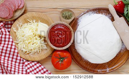 dough, tomato sauce, cheese, sausage - the ingredients for pizza