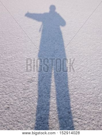 The shadow of a man on white snow