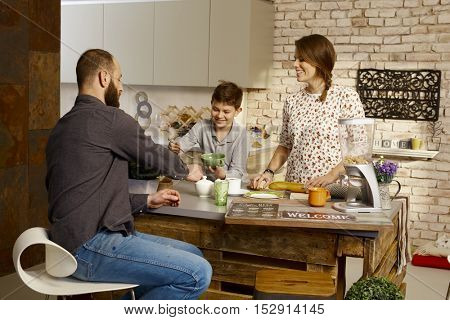 Happy family having breakfast in the kitchen.