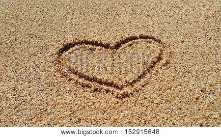 Drawing of abstract heart in the sand on beach