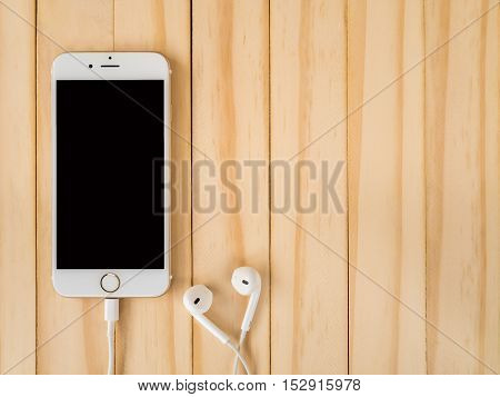 CHIANGRAI THAILAND -SEPTEMBER 15 2016: Front view of new Apple iPhone 7 mockup and new Apple EarPods mockup on wooden background with copy space.