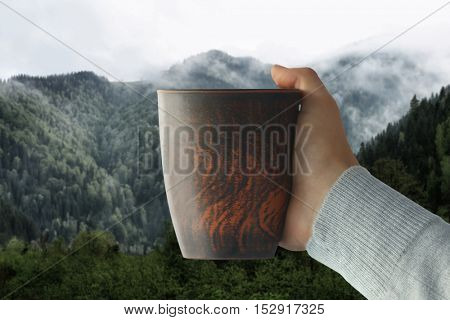 Male hand holding cup of coffee on misty mountains background.