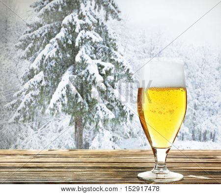 Glass of beer on wooden table against winter nature background.