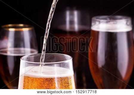 pouring beer into glass on wooden table.