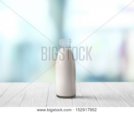 Glass bottle of milk on white wooden table against blurred background. Dairy concept.