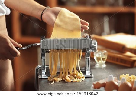 Man using pasta machine to prepare tagliatelle, close up view