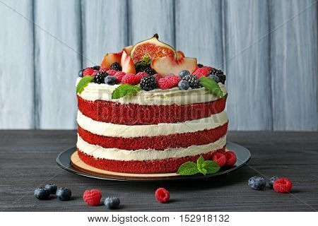 Tasty cake with berries on wooden background