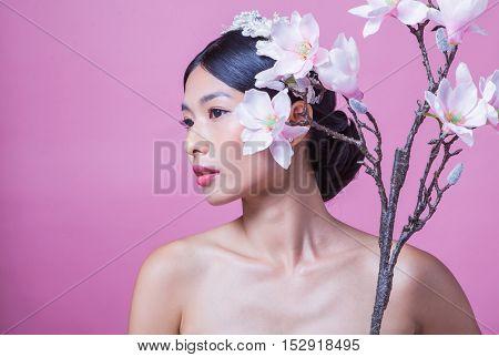 Portrait of confident bride holding artificial flowers against pink background