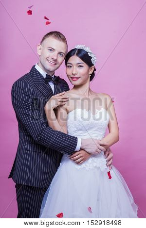 Loving bride and groom holding each other while standing against pink background with rose petals falling from the ceiling