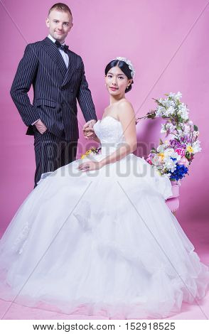 Beautiful inter racial couple looking to camera  whilst the Chinese girl sites on a flower chair against a pink background