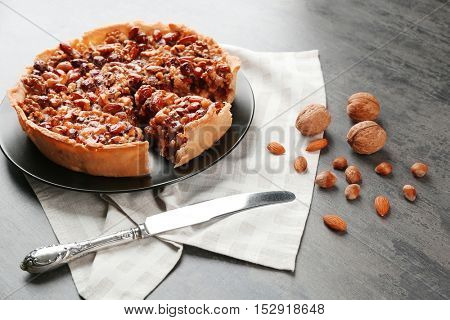 Delicious cake with nuts on table