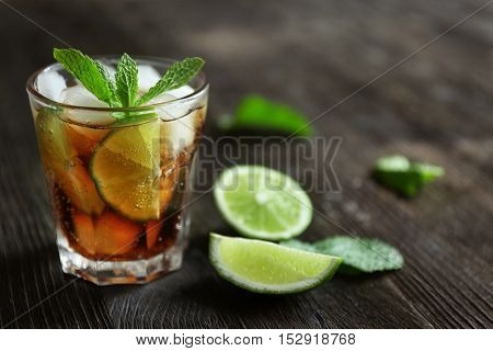 Glass of cocktail with ice and mint on wooden table closeup