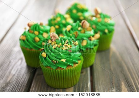Green pistachio cupcakes on wooden background