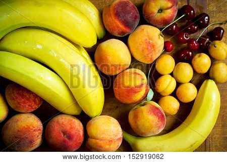 Ripe bananas, peaches, apricots and sweet cherry on a wooden table, top view