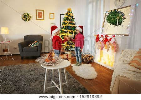 Cute little kids in Santa hats with Christmas gifts at home