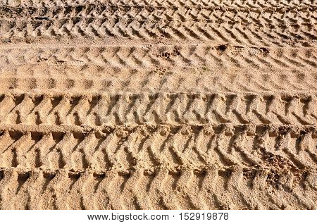 Texture of yellow sand with traces of tractor wheels in perspective closeup. Abstract pattern.