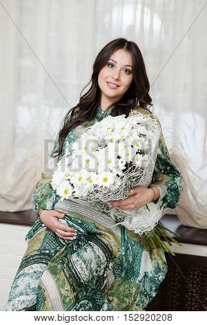 Pretty pregnant woman with chamomiles flowers. Home