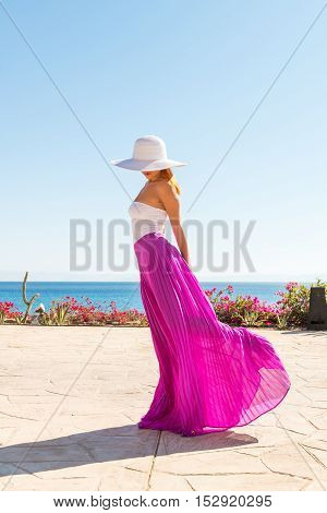 Photo of  beautiful young woman in a hat at sea resort