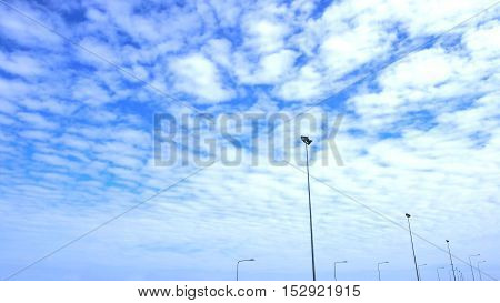 Very nice Fluffy clouds filled the blue sky and the light pole lined while shooting in a car moving on the way.