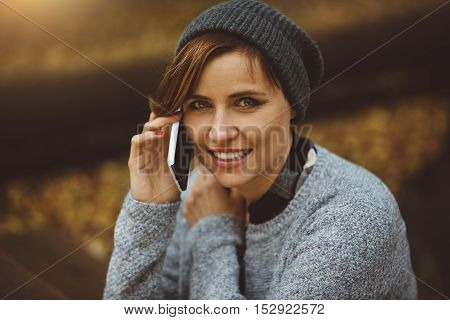 Portrait of smiling and happy young millenial woman sitting alone in the forest and talking with smartphone.