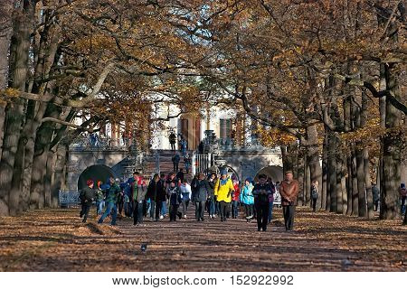 TSARSKOYE SELO, SAINT - PETERSBURG, RUSSIA - OCTOBER 19, 2016: Group of children with teachers walk on the alley near Ramp in Catherine Park next to The  Cameron Gallery