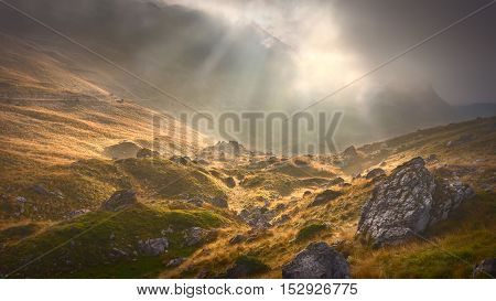 Unpredictable weather conditions in the beauty of wild mountain terrain with sunbeams in the background.