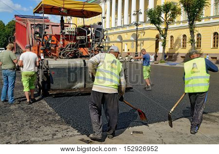 23.08.2015.Russia.Saint-Petersburg.Workflow for laying new asphalt.The weather is very hot.
