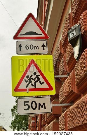 Traffic signs attached to the wall of the house.