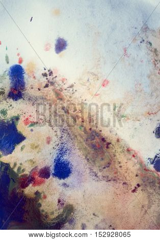 Drops with streaks of different colors of paint are mixed and absorbed. Abstract paint stains on white paper