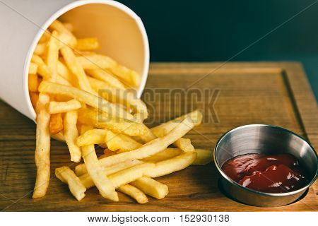 Fresh Fried French Fries  In A Paper Container With Ketchup On Wooden Background