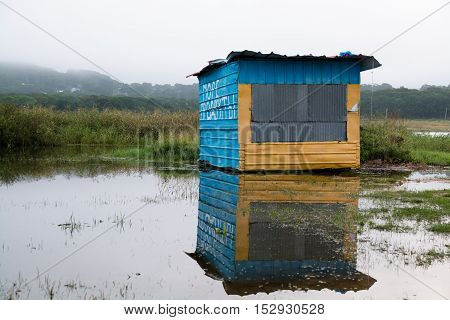 Lonely bright coloured metal booth standing in the middle of flooded field