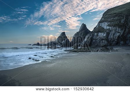 Stunning Colorful Sunset Over Beach Landscape With Jagged Rock Formations