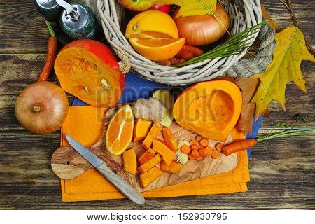 Fresh ingredients for pumpkin soep with apple orange carrot and onion on wooden background