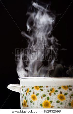Rising steam above vintage saucepan on black background