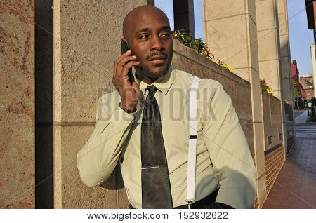 Professional man speaking on cellular phone outside office building
