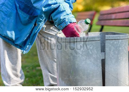 Person Scrounging Through A Bin