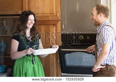 couple in traditional bavarian clothes standing at stove in kitchen and laughing