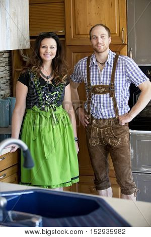 couple in traditional bavarian clothes standing in kitchen and looking at camera