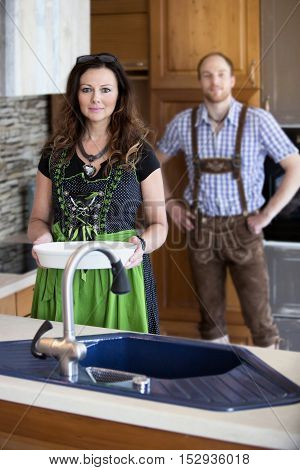 couple in traditional bavarian clothes standing in kitchen