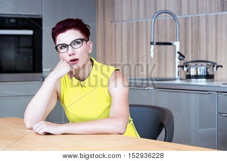 woman in yellow dress sitting at kitchen table looking upset