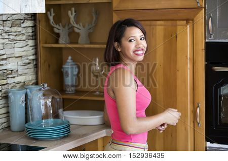 beautiful hispanic woman standing in kitchen and smiles at camera