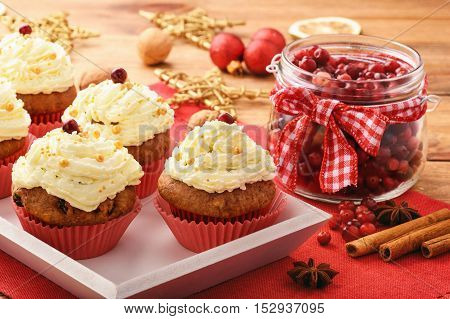Chocolate cupcakes with cranberries on christmas festive table.